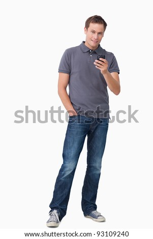 Young man holding his cellphone against a white background