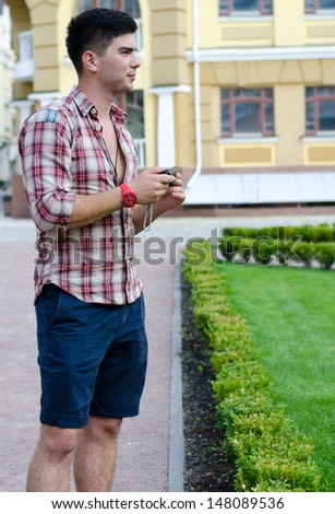 Young man holding his compact digital camera while sightseeing alone in an urban environment - stock photo