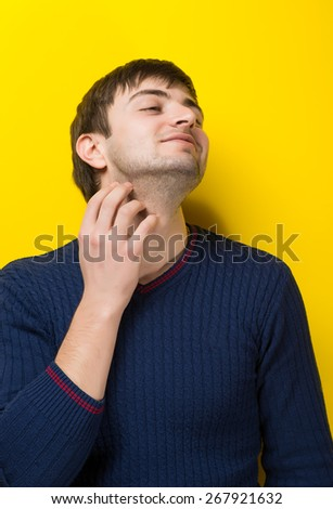 young man holding his hand on the necks yellow background - stock photo