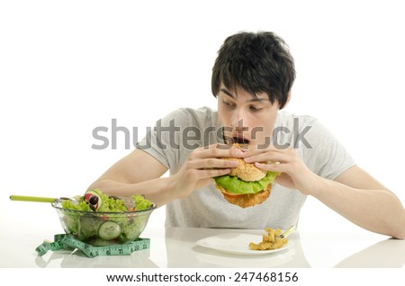 Young man holding in front a bowl of salad and a big hamburger. Choosing between good healthy food and bad unhealthy food. Organic food versus fast food - stock photo