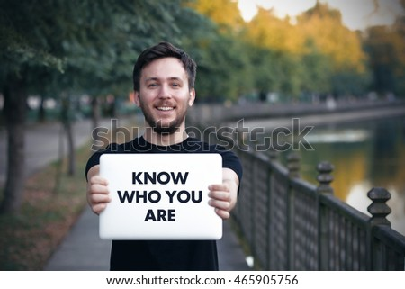 Young man holding  Know Who You Are  sign