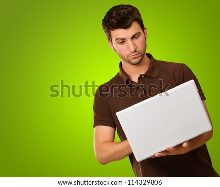 Young Man Holding Laptop On Green Background