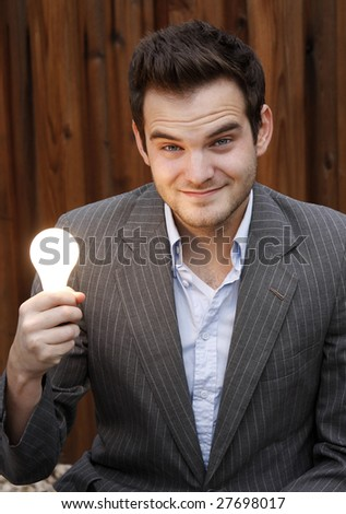 Young man holding light bulb. - stock photo