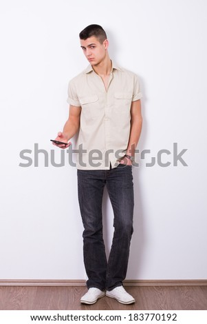 young man holding mobile - stock photo