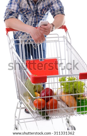 Young man holding mobile phone and shopping cart close up