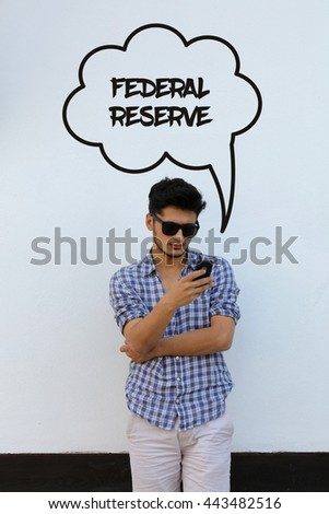 Young man holding mobile phone writen Federal Reserve on it - stock photo