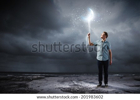 Young man holding moon balloon against dark background - stock photo