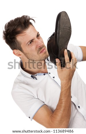 Young man holding one of his shoes close to his nose pulling a face, isolated over white - stock photo