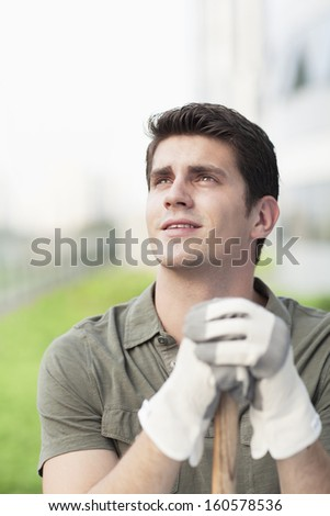 Young man holding rake and looking into distance on roof top garden in the city - stock photo