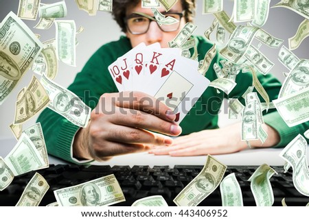 Young man holding royal flash poker cards with keyboard on table and abstract dollar bill rain. Gambling concept - stock photo