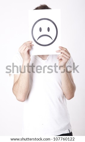 Young man holding sad smiley face. - stock photo
