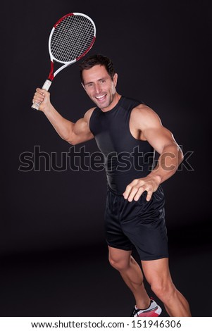 Young Man Holding Tennis Racket Isolated On Black Background - stock photo