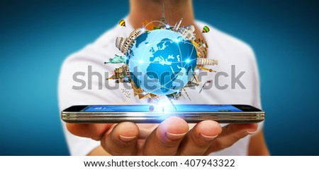 Young man holding the planet earth surrounded by famous monuments of the world over his mobile phone - stock photo