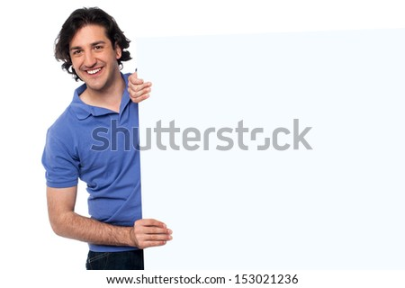 Young man holding up blank white billboard - stock photo