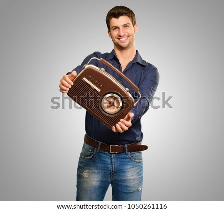 Young Man Holding Vintage Radio On Gray Background