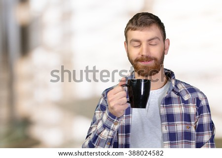 Young man holding warm cup of tea/coffee