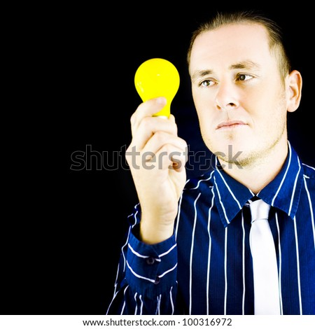 Young man holding yellow bulb in his hand on black background with copy space - stock photo