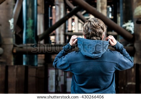 young man holds hands hood while standing under the bridge - stock photo