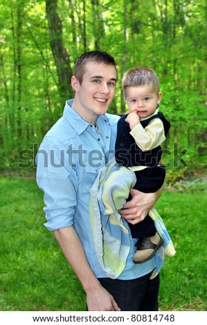 Young man holds little boy surrounded by green forest.  Man is smiling and toddler is chewing on his finger. - stock photo