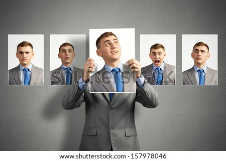 young man holds up a photograph hanging on the wall behind the additional photos with different emotions - stock photo