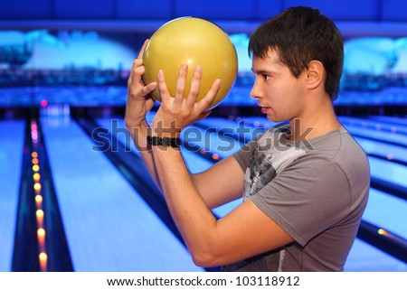 Young man holds yellow ball and prepares to throw in bowling; profile of man