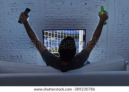 young man home alone watching soccer or football game in television enjoying and celebrating goal and victory holding beer bottle and TV controller gesturing on the sofa happy and excited - stock photo