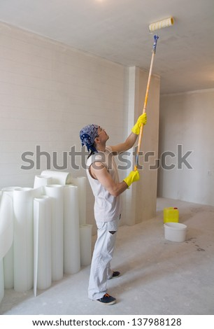 Young man - house painter worker painting ceiling with painting roller