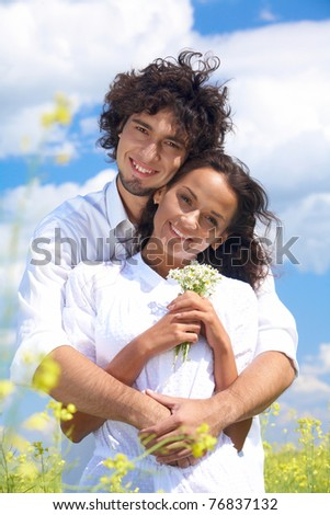 Young man hugging charming lady in white clothing while both looking at camera with happy smiles - stock photo