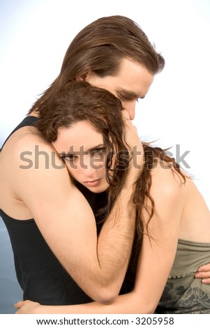 young man hugs and comforts young female in tears - stock photo