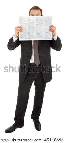 young man in a black business suit reads the newspaper on a white background - stock photo