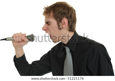 Young man in a black suit and tie screams his emotional guts out into the microphone singing. - stock photo