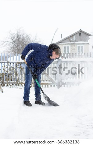Young man in a blue jacket removes snow shovel in the yard of a black