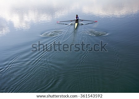 Young man in a boat, rowing on the tranquil lake - stock photo