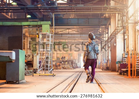 Young man in a factory in protective workwear - stock photo
