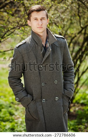 young man in a gray coat stands on a background of trees