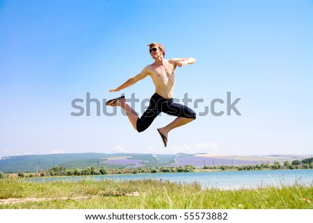 Young man in a green landscape jumping