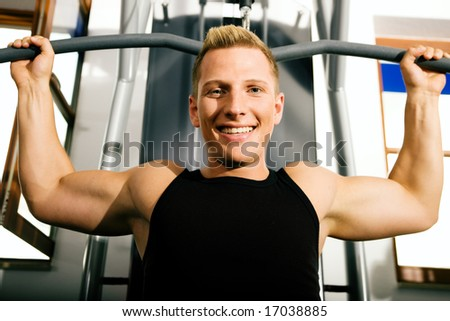Young man in a gym training his back muscles on a machine - stock photo