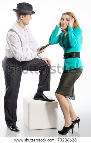 young man in a hat threatens gun attractive girl - stock photo