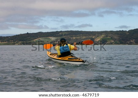 Young man in a kayak paddling