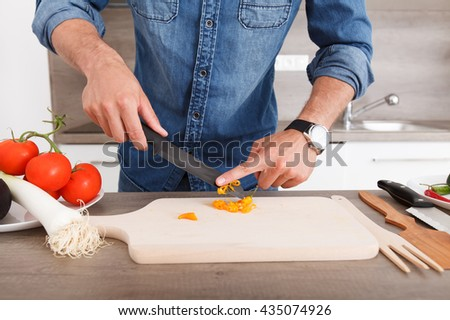 Young man in a modern kitchen preparing a vegetable salad. Nice man shows off his cooking skills. - stock photo