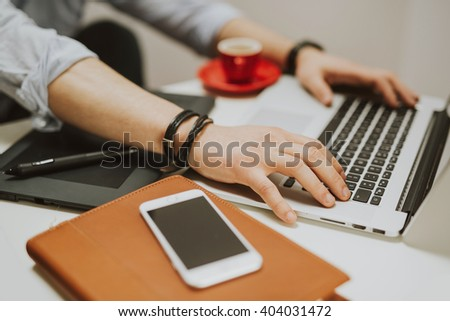 Young man in a modern office design sketching construction project design on a tablet, laptop and drinks coffee - stock photo