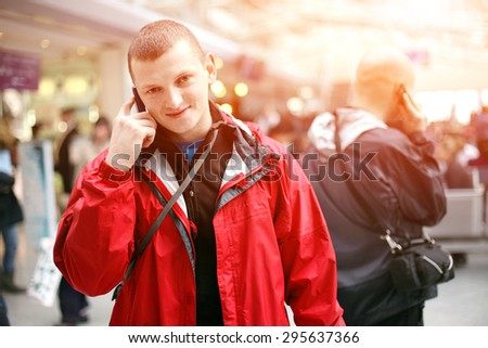 Young man in a red jacket calling on the phone at the airport. another caller man in the background. - stock photo
