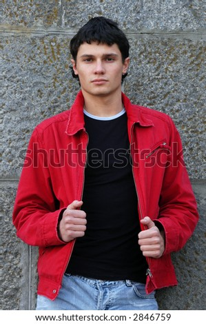Young man in a red jacket in front of a stonewall - stock photo