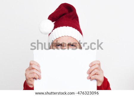 Young man in a red knitted Santa Claus cap holding a blank piece of paper. He has a serious look.