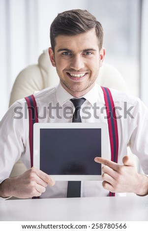 Young man in a suit holding a tablet before. - stock photo