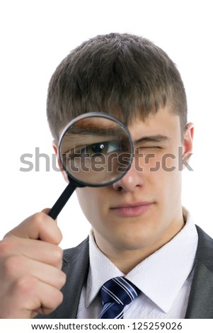 Young man in a suit looks through a magnifying glass on a white background