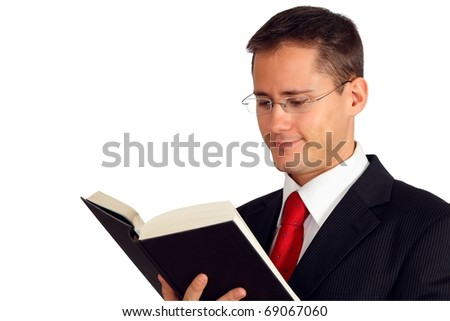 Young man in a suit reading a book - stock photo