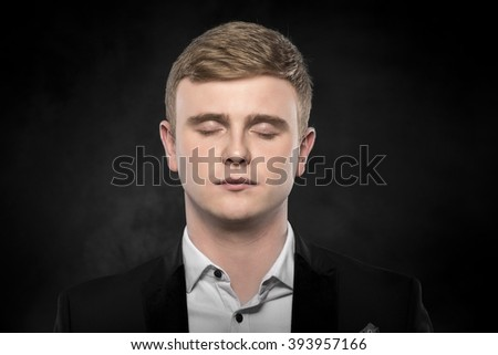 Young man in a suit with his eyes closed. Sleeps.