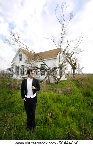 Young man in a tuxedo standing on front of an abandoned house. - stock photo
