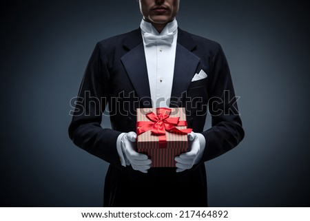 Young man in a tuxedo with a gifts - stock photo